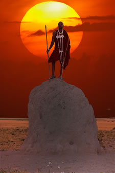 Maasai warrior standing atop termite mound at sunset